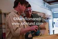 Photo of two men sanding a piece of wood in a cabinet maker small business.